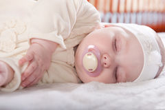 Sleeping baby. Cute baby girl is sleeping near her bed Stock Photo