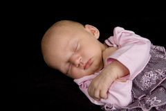 Sleeping Baby. A sleeping baby on a black background stock image