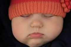 Sleeping baby. Close-up sleeping baby with orange hat Stock Images