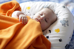 Sleeping baby. The baby boy sleeping under a orange blanket at home Royalty Free Stock Photo