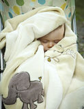Sleeping baby. Baby wrapped up in a blanket and sleeping in a stroller Royalty Free Stock Image