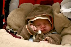 Sleeping baby. A sleeping new born baby in winter clothes Royalty Free Stock Image