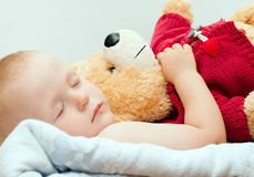 Sleeping baby with bear Stock Images