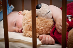 Sleeping baby with bear toy Royalty Free Stock Images