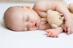 Sleeping baby in bed, holding a teddy bear. Royalty Free Stock Photography