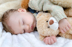 Sleeping baby. Baby sleeping on a blanket with stuffed animal in her arms Stock Photo