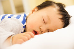 Sleeping baby boy on the bed Royalty Free Stock Photography