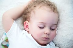 Baby boy blond with curls sleeping in his bed stock image