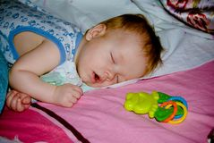 Sleeping baby boy face down at home with a toy. Portrait of an infant at home Stock Photography