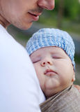 Sleeping baby boy in sling, father carrying son Stock Photo