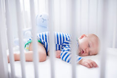 Sleeping baby boy in white crib Stock Image
