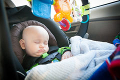 Sleeping Baby in Carseat. Baby with full pouty lips and a cute little nose sleeping in a car seat Royalty Free Stock Photography