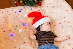 Sleeping baby by Christmas tree, wearing Santa Claus hats Stock Image