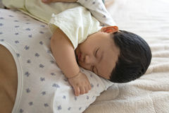 Sleeping baby. Closeup of a woman with cute baby sleeping in her arms Stock Photography