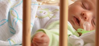 Sleeping baby in a cot Stock Photos