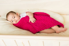 Sleeping baby covered with knitted blanket Stock Images