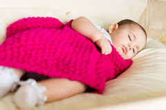Sleeping baby covered with knitted blanket Stock Photography
