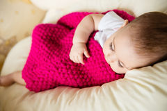 Sleeping baby covered with knitted blanket Stock Photos