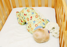 Sleeping Baby in Crib. Blond baby boy sleeping on his stomach in a drop side crib with his blanket and pacifier.  Cute animal PJ's with blue, green, red and Stock Photo