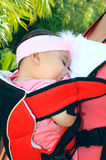 Sleeping baby girl. In the backpack Royalty Free Stock Photo