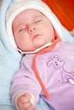 Sleeping baby girl. Portrait of cute baby girl sleeping in cosy hat Royalty Free Stock Image