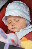 Sleeping baby girl. Seven months old baby girl sleeping in her pushchair during a walk Royalty Free Stock Photography