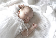 Sleeping Baby Girl. New born baby girl dressed in white asleep on a white blanket Royalty Free Stock Images
