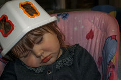 Sleeping baby girl with blond hair. Blond baby girl asleep on a baby swing with a plastic toy box on her head as a hat. She wears a pink fur sweater Royalty Free Stock Image