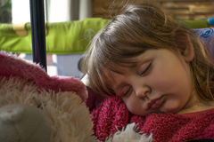 Sleeping baby girl with blond hair. Blond baby girl wearing a pink fur sweater asleep on a chair with a furry teddy bear on her lap Stock Image