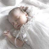Sleeping Baby Girl. New born baby girl dressed in white asleep on a white blanket Royalty Free Stock Photography
