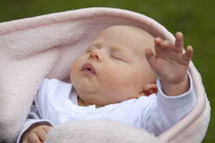 Sleeping baby girl reaching out hand Stock Photo