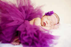 A sleeping baby girl is sleeping and wearing purple yarn soft focus Royalty Free Stock Photography