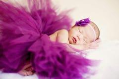 A sleeping baby girl is sleeping and wearing purple yarn soft focus. A sleeping baby girl wearing purple yarn Royalty Free Stock Photography