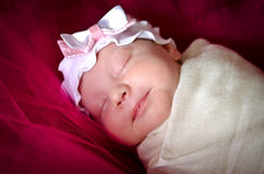 Sleeping baby girl in a sling on her head Royalty Free Stock Image