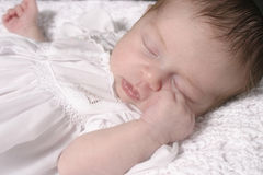 Sleeping Baby Girl in White Dress Stock Photography