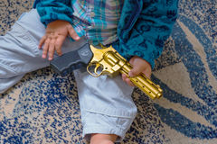 Sleeping baby with a gun in his hands Stock Photography