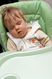 Sleeping baby in high chair Stock Photos