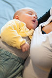 Sleeping baby in his mother's arms Stock Images