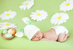 Sleeping baby infant as rabbit and Easter eggs. Small baby with a rabbit ears. Lying on his stomach. Near a basket with Easter eggs Stock Photo
