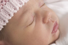 Sleeping baby with knitted hat. Portrait of contented looking two week old sleeping baby girl wearing  pink knitted hat Stock Image
