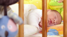 Sleeping baby. Mother puts a toy in the bed of her sweet sleeping baby stock video