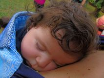 Sleeping baby. On mother`s chest in wrap sling Stock Photography