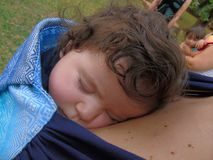 Sleeping baby. On mother`s chest in wrap sling Stock Photos