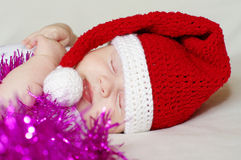 Sleeping baby in New Year's hat among spangle Royalty Free Stock Photo