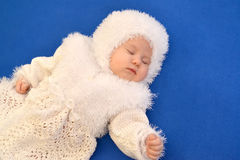 The sleeping baby in a New Year's suit of the Snowflake on a blue background. The sleeping baby in a New Year's suit of the Snowflake stock photos