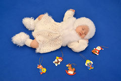 The sleeping baby in a New Year's suit of the Snowflake with Chr. Istmas tree decorations on a blue background royalty free stock photos