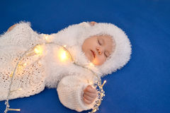 The sleeping baby in a New Year's suit of the Snowflake with the shining garland in the form of heart on a blue background Royalty Free Stock Images