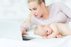 Sleeping baby next to mother using laptop Stock Photography