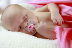 Sleeping baby with pacifier. A close-up of a baby girl falling asleep with a pacifier in her mouth Stock Photo