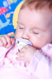 Sleeping baby with pacifier. Portrait of sleeping baby girl in pink clothes with pacifier or dummy royalty free stock photography